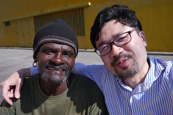 ロサンゼルスのホームレスと新宅睦仁が肩を組んで笑っている写真