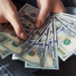 アメリカドルのお札を複数枚、手で広げている画像
